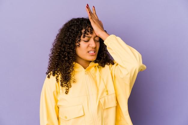 Jonge afro-amerikaanse afro vrouw geïsoleerd iets vergeten, voorhoofd slaan met palm en ogen sluiten.