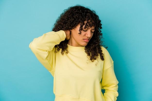 Jonge afro-amerikaanse afro vrouw geïsoleerd met nekpijn als gevolg van stress, masseren en aanraken met de hand.