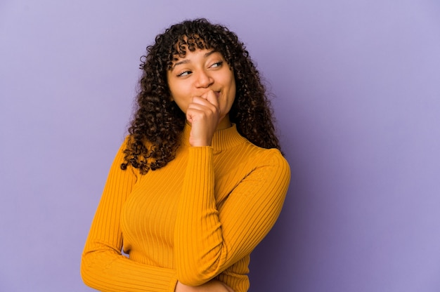 Jonge afro-amerikaanse afro vrouw geïsoleerd ontspannen denken aan iets kijken naar een kopie ruimte.