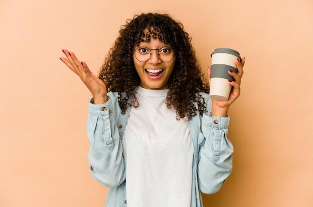 Jonge afro-amerikaanse afrovrouw die een afhaalkoffie houdt die een aangename verrassing ontvangt, opgewonden en handen opheft.