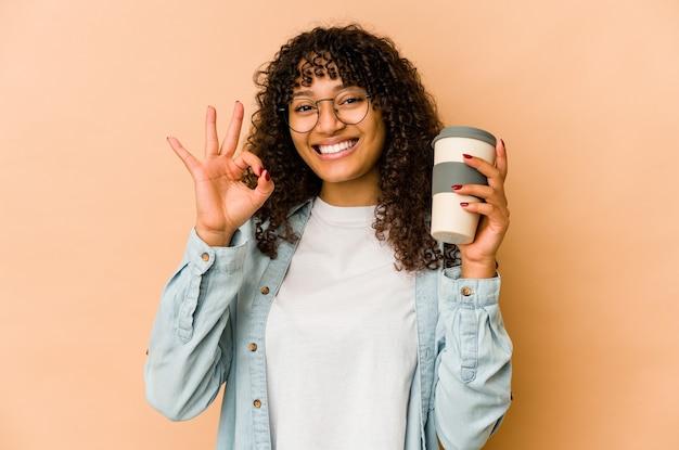 Jonge afro-amerikaanse afrovrouw die een afhaalmaaltijden koffie houdt, vrolijk en zelfverzekerd tonend ok gebaar.