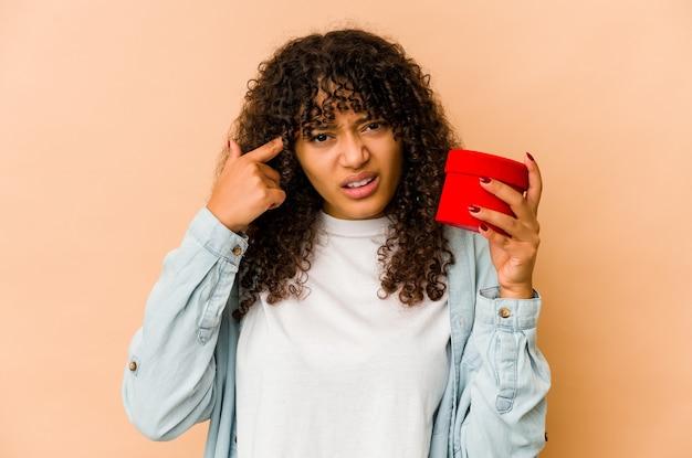Jonge afro-amerikaanse afrovrouw die een gift van de valentijnskaartendag houdt die een teleurstellinggebaar met wijsvinger toont.