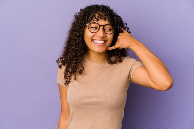 Jonge afro-amerikaanse afrovrouw die een gsm-gebaar met vingers toont.