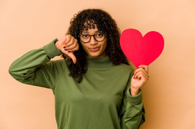 Jonge afro-amerikaanse afrovrouw die een hart van de valentijnskaartendag houdt dat een afkeergebaar, duimen naar beneden toont. meningsverschil concept.