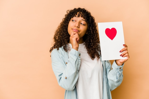 Jonge afro-amerikaanse afrovrouw die een kaart van de valentijnskaartendag houdt die zijwaarts met twijfelachtige en sceptische uitdrukking kijkt.
