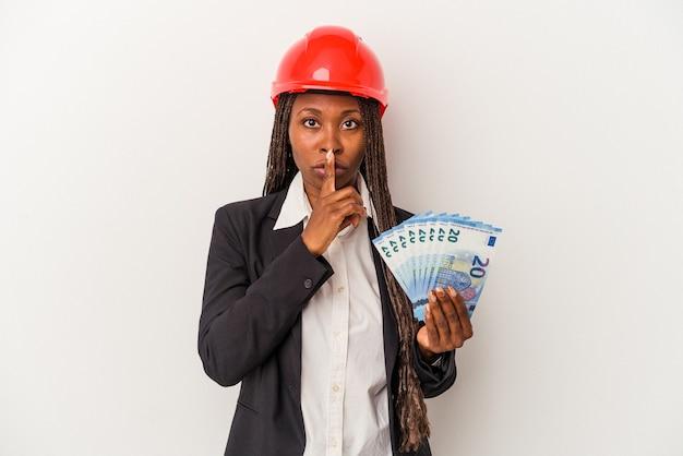 Jonge afro-amerikaanse architectenvrouw die rekeningen houdt die op een witte achtergrond worden geïsoleerd en een geheim houdt of om stilte vraagt.