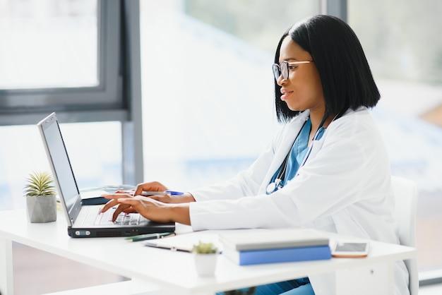Jonge afro-amerikaanse arts die op laptop in de kliniek werkt