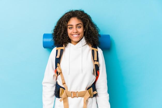 Jonge afro-amerikaanse backpacker vrouw blij, lachend en vrolijk.