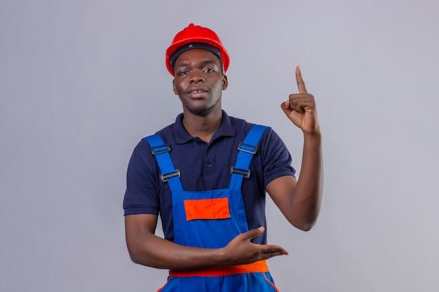 Jonge afro-amerikaanse bouwersmens die bouwuniform en veiligheidshelm draagt die vinger omhoog wijst en met handpalm met zelfverzekerde uitdrukking staande presenteert