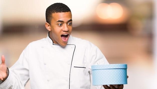 Jonge afro amerikaanse chef-kok man met geschenk doos in handen op ongericht achtergrond