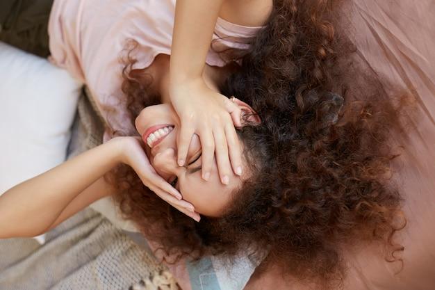 Jonge afro-amerikaanse dame geniet van de zonnige dag thuis en lacht, brengt ze vrije dag thuis door, tegens gezicht met handen en liggend op het bed.