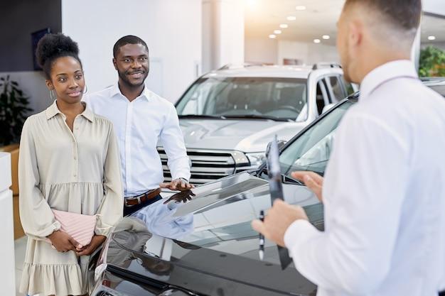 Jonge afro-amerikaanse echtpaar kwam naar auto kijken voor toekomstige aankoop