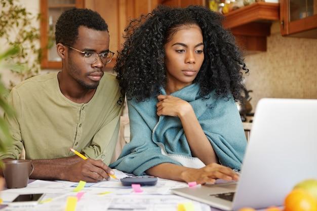 Jonge afro-amerikaanse familie die papierwerk samen doet