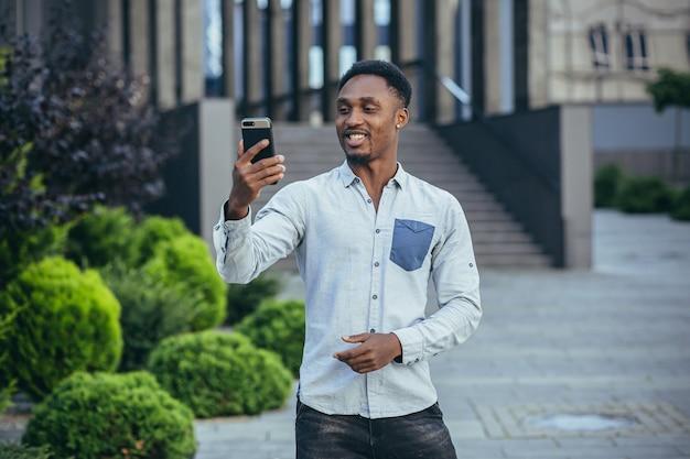 Jonge afro-amerikaanse freelancer praten over video-oproep in de buurt van kantoor vrolijk lachende man