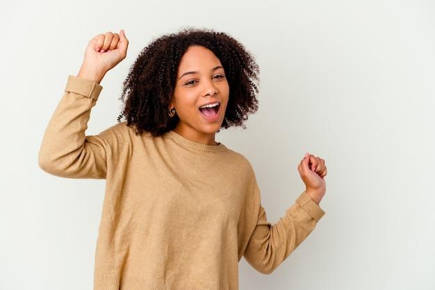Jonge afro-amerikaanse gemengd ras vrouw geïsoleerd dansen en plezier maken.