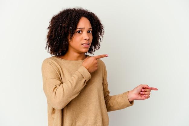 Jonge afro-amerikaanse gemengd ras vrouw geïsoleerd geschokt wijzend met wijsvingers naar een kopie ruimte.