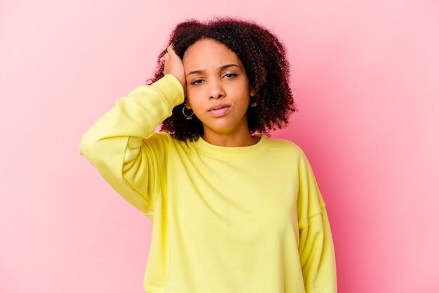 Jonge afro-amerikaanse gemengd ras vrouw geïsoleerd moe en erg slaperig hand op het hoofd houden.