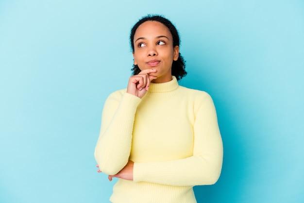 Jonge afro-amerikaanse gemengd ras vrouw geïsoleerd zijwaarts kijken met twijfelachtige en sceptische uitdrukking.