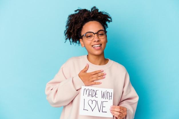 Jonge afro-amerikaanse gemengd ras vrouw met een gemaakt met liefde concept lacht hardop hand op de borst te houden.