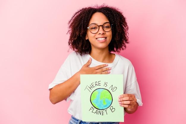 Jonge afro-amerikaanse gemengd ras vrouw met een wereld bescherming concept karton lacht hardop hand op de borst te houden.