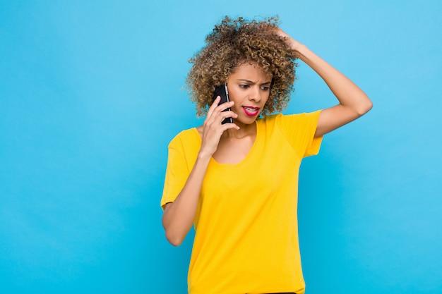 Jonge afro-amerikaanse gevoel verbaasd en verward, hoofd krabben en op zoek naar de kant met een mobiele telefoon