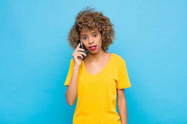 Jonge afro-amerikaanse gevoel verbaasd en verward, met een domme, verbijsterde uitdrukking op zoek naar iets onverwachts met een mobiele telefoon