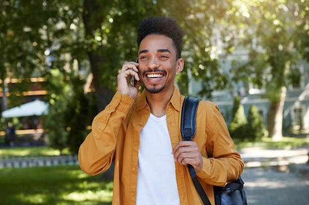 Jonge afro-amerikaanse glimlachende jongen wandelen na studie in het park, praten aan de telefoon, draagt in een geel shirt en een wit t-shirt met een rugzak op een schouder, glimlachend en geniet van de dag.