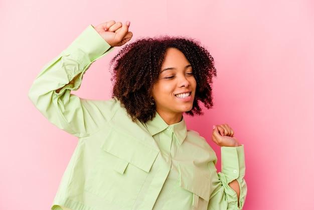 Jonge afro-amerikaanse halfbloed geïsoleerde vrouw viert een speciale dag, springt en heft de armen op met energie.