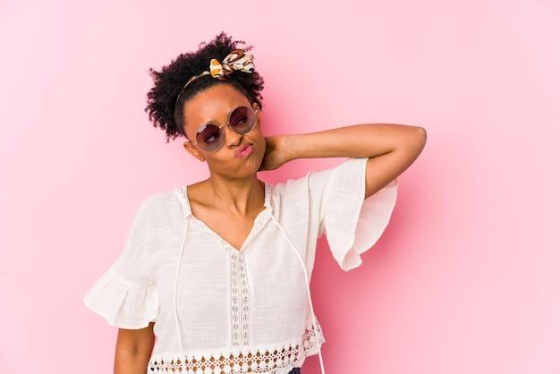 Jonge afro-amerikaanse hipster vrouw geïsoleerd achterkant van het hoofd aanraken, denken en een keuze maken.