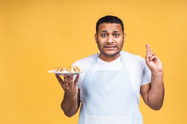 Jonge afro-amerikaanse indiase zwarte man die sushi eet met stokjes over geïsoleerde gele achtergrond. kok bereiden van sushi.