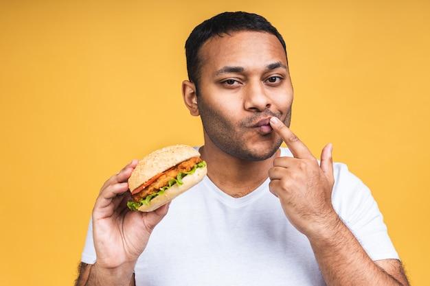 Jonge afro-amerikaanse indiase zwarte man eten hamburger geïsoleerd op gele achtergrond. dieet concept.