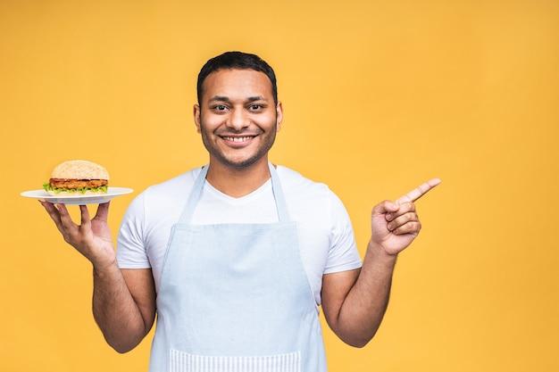 Jonge afro-amerikaanse indiase zwarte man eten hamburger geïsoleerd op gele achtergrond. kok bereiden hamburger. wijzende vinger.