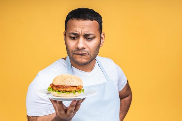 Jonge afro-amerikaanse indiase zwarte man eten hamburger geïsoleerd op gele achtergrond. kok bereiden hamburger.