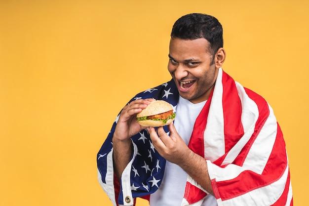 Jonge afro-amerikaanse indiase zwarte man eten hamburger geïsoleerd op gele achtergrond met amerikaanse vlag. dieet concept.