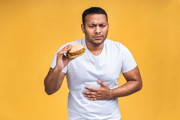 Jonge afro-amerikaanse indiase zwarte man eten hamburger geïsoleerd op gele achtergrond. ongezond eten, maagpijn.