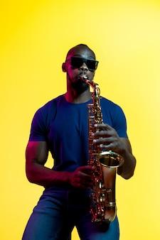 Jonge afro-amerikaanse jazzmuzikant die de saxofoon op geel speelt