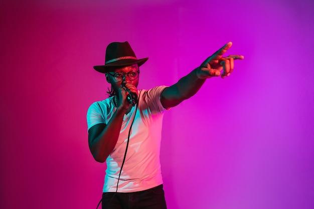 Jonge afro-amerikaanse jazzmuzikant die een roze liedverloop zingt