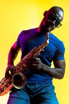 Jonge afro-amerikaanse jazzmuzikant saxofoon spelen op gele achtergrond in trendy neonlicht.