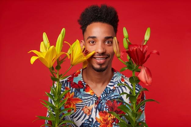 Jonge afro-amerikaanse jongen, draagt in hawaiiaans shirt, kijkt naar de camera met gelukkige uitdrukking, staat op rode achtergrond met gele en rode bloemen en glimlacht.