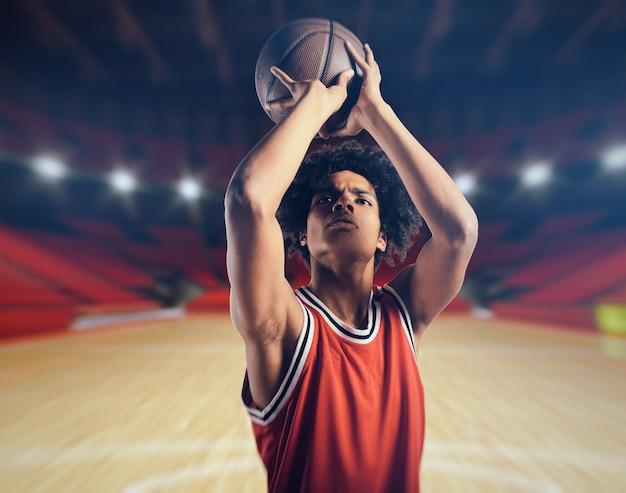 Jonge afro-amerikaanse jongen met basketbal nemen van een vrije worp