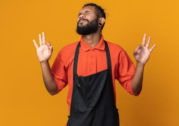 Jonge afro-amerikaanse kapper die een uniform draagt en een goed teken doet met gesloten ogen