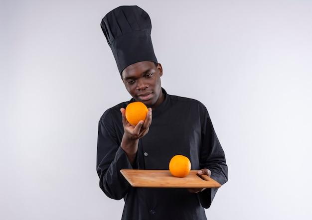 Jonge, afro-amerikaanse kok in chef-kok uniform houdt oranje op snijplank en bij de hand op wit met kopie ruimte