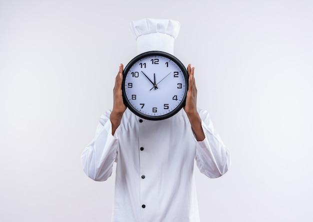 Jonge afro-amerikaanse kok in uniform chef-kok sluit gezicht met klok geïsoleerd op een witte achtergrond met kopie ruimte