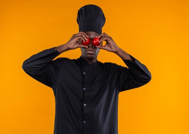Jonge afro-amerikaanse kok in uniform chef-kok sluit ogen met tomaten op oranje met kopie ruimte