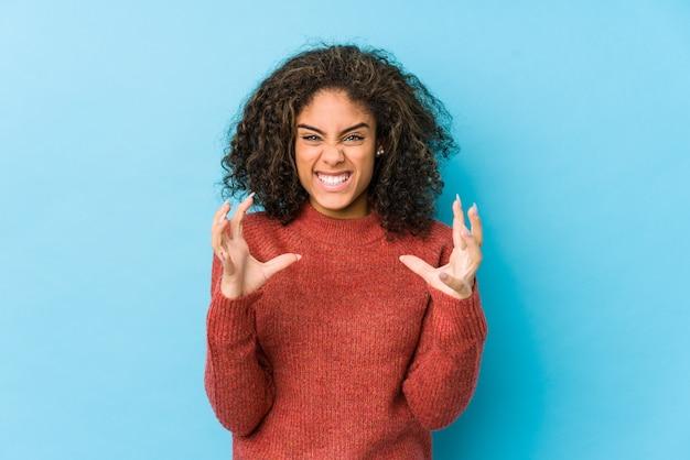 Jonge afro-amerikaanse krullende haar vrouw boos schreeuwen met gespannen handen.