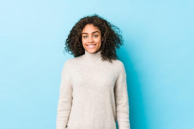 Jonge afro-amerikaanse krullende haarvrouw blij, glimlachend en vrolijk.