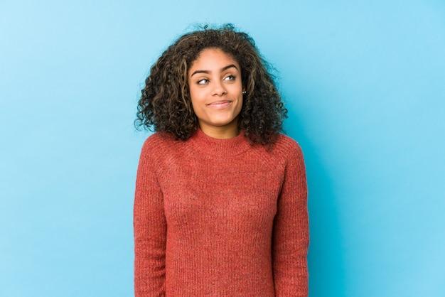 Jonge afro-amerikaanse krullende haarvrouw die droomt van het bereiken van doelen en doeleinden