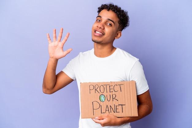 Jonge afro-amerikaanse krullende man geïsoleerd houden een bescherm onze planeet glimlachend vrolijk tonend nummer vijf met vingers.