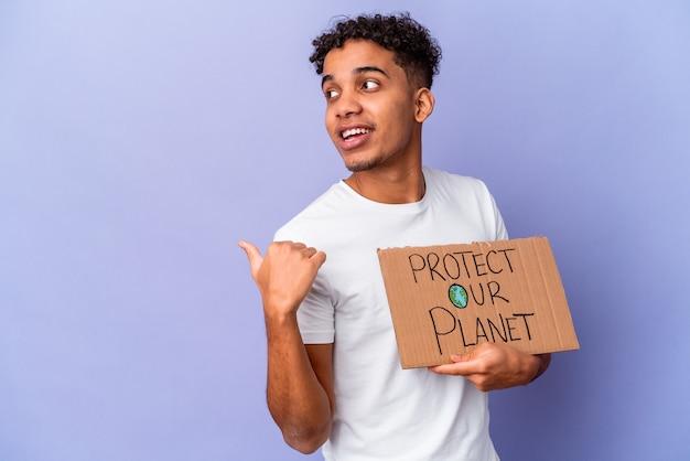 Jonge afro-amerikaanse krullende man geïsoleerd houden een bescherming van onze planeet wijst met duimvinger weg, lachend en zorgeloos