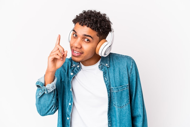 Jonge afro-amerikaanse krullende man geïsoleerd luisteren naar muziek met een koptelefoon met een idee, inspiratie concept.